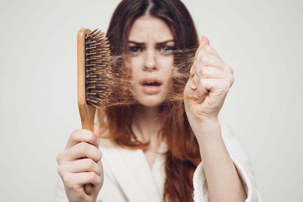 Kobieta trzyma szczotkę do włosów w ręku i wyciąga z niej włosy.